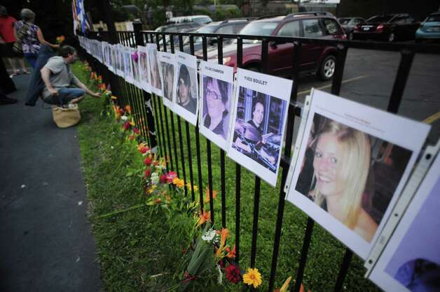 Flowers are placed beneath the photographs of those killed in the Lac Megantic oil train disaster  during a vigil at the Ezra Prentice Homes on Sunday, July 6, 2014, in Albany, N.Y., to remember the Lac Megantic oil train disaster that occurred a year ago in which 47 people died when a runaway train derailed and exploded. (Paul Buckowski / Times Union) ORG XMIT: MER2014070621233461 Photo: Paul Buckowski / 00027626A