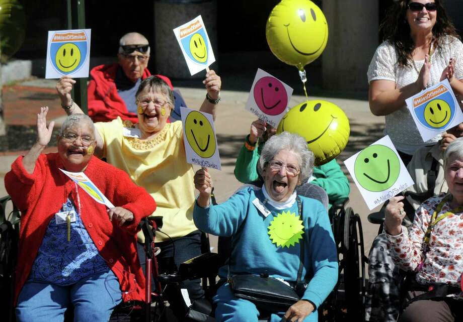 Eddy Senior Care residents and workers line State Street to celebrate Miles of Smiles on Wednesday, Aug. 12, 2015, in Schenectady, N.Y. Residents  and employees were invited to bring signs and banners and wear shirts to represent their neighborhoods, schools and businesses and show their city pride. (Cindy Schultz / Times Union) Photo: Cindy Schultz / 00032941A