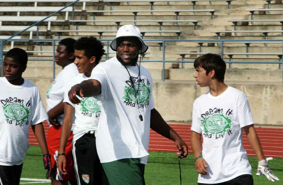 In this photo taken July 11, 2015, former Pflugerville High School football standout IK Enemkpali, center, gives directions before a drill at his annual football camp at Kuempel Stadium in Pflugerville, Texas. Enemkpali, an outside linebacker in his second season, was immediately released by the New York Jets after punching quarterback Geno Smith and breaking his jaw, Tuesday, Aug. 11, 2015. (Joe Harrington/Austin American-Statesman via AP)  AUSTIN CHRONICLE OUT, COMMUNITY IMPACT OUT, INTERNET AND TV MUST CREDIT PHOTOGRAPHER AND STATESMAN.COM, MAGS OUT; MANDATORY CREDIT ORG XMIT: TXAUS201 Photo: Joe Harrington / Austin American-Statesman