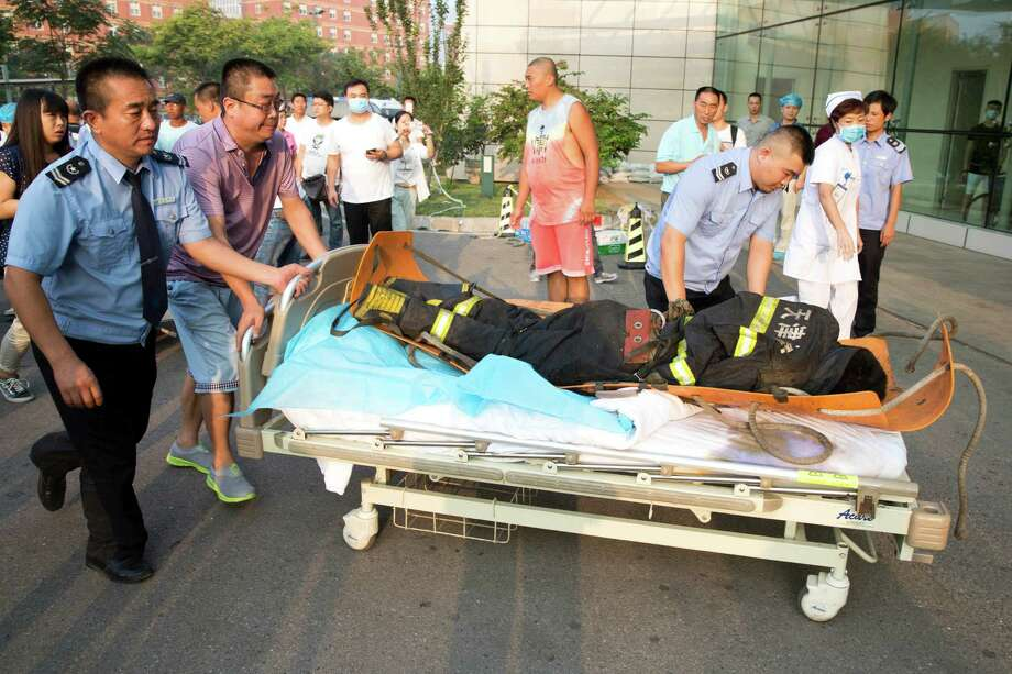 Security guards and a resident push what appears to be a lifeless body into a hospital in northeastern China's Tianjin municipality, Thursday, Aug. 13, 2015. Huge explosions sparked overnight at a warehouse for dangerous materials in the northeastern Chinese port of Tianjin killed at least 13 people, injured hundreds and sent massive fireballs into the night sky, officials and state media outlets said Thursday. (AP Photo/Ng Han Guan) ORG XMIT: XHG105 Photo: Ng Han Guan / AP