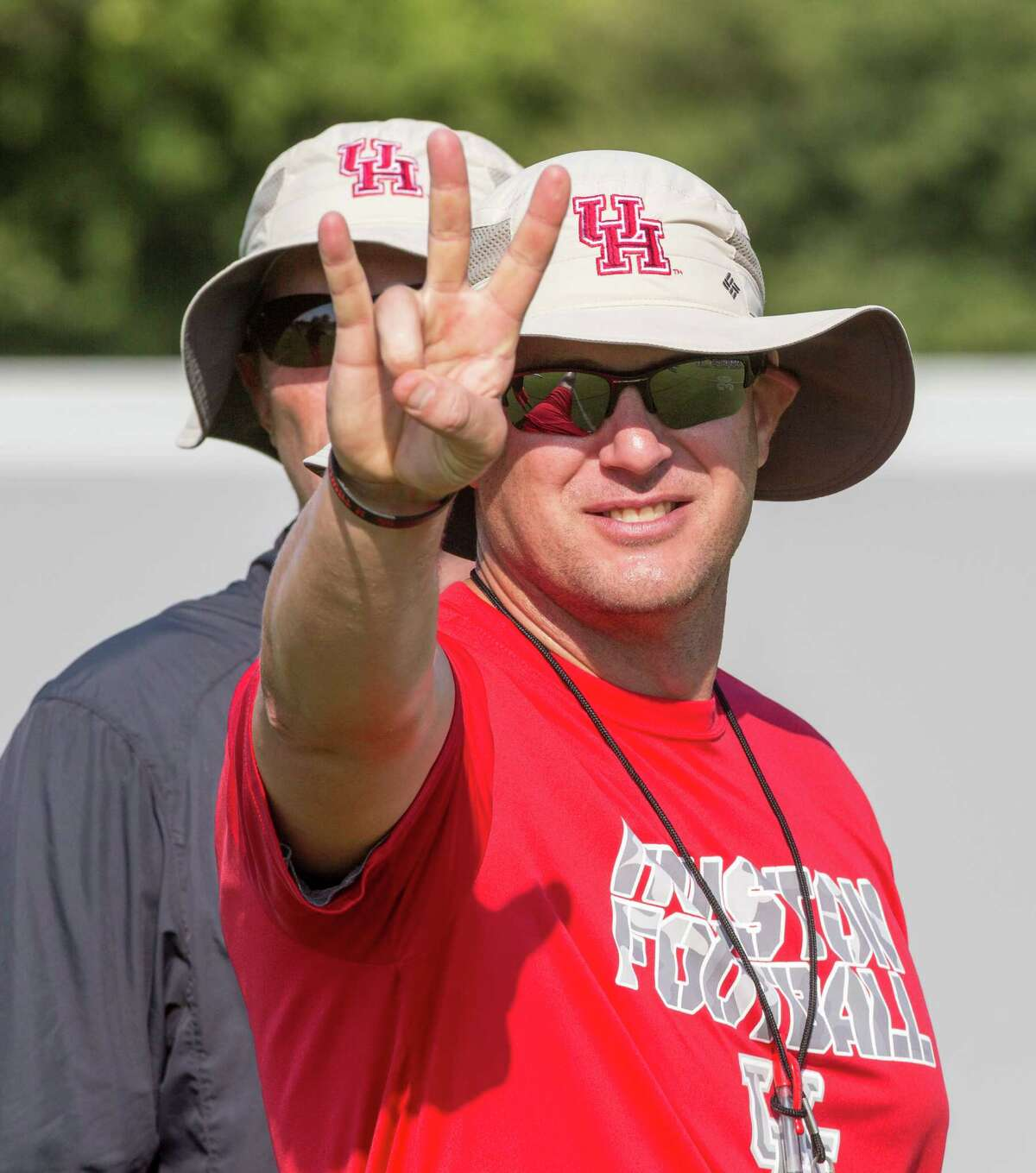UH football practice. UH practice field behind Alumni Athletic Office, UH campus. ID: An upbeat Tom Herman, Head Coach, flashes the traditional UH hand gesture during practice. Tuesday August 11, 2015 (Craig H. Hartley/For the Chronicle)
