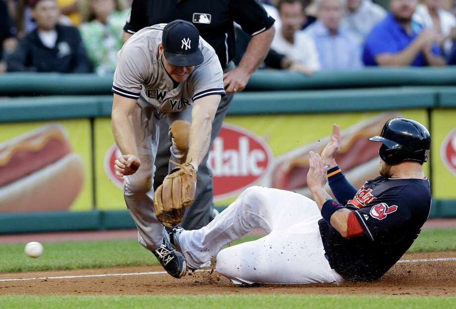 Cleveland Indians' Roberto Perez, right, slides safely into third base as New York Yankees' Chase Headley can't get to the ball during the third inning of a baseball game, Wednesday, Aug. 12, 2015, in Cleveland. Perez was safe on the play. (AP Photo/Tony Dejak) ORG XMIT: OHTD105 Photo: Tony Dejak / AP