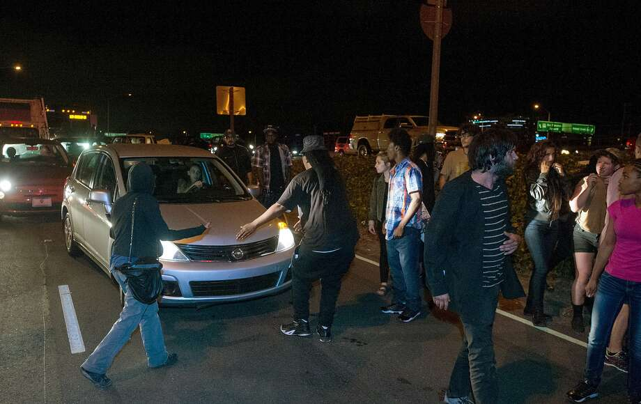 Protesters block traffic on a freeway offramp in Oakland on Wednesday, August 12, 2015. More than 50 people demonstrated, some throwing eggs and other projectiles at officers, in response to an officer involved shooting that fatally wounded a 24-year-old armed robbery suspect. (JOSH EDELSON / SPECIAL TO THE CHRONICLE) Photo: Josh Edelson, JOSH EDELSON / SAN FRANCISCO CHR