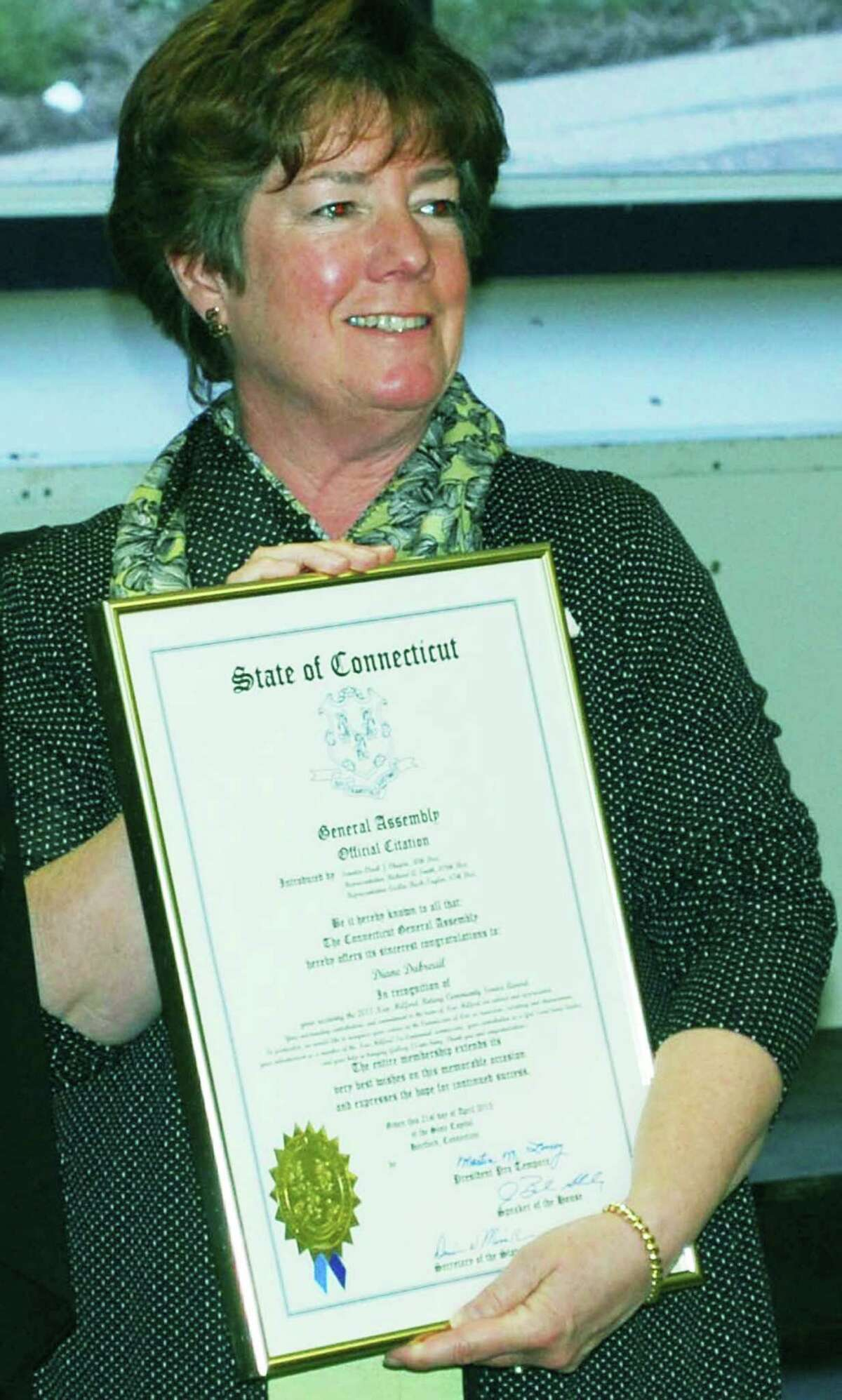 New Milford resident Diane Dubreuil is presented a certificate of recognition from the state General Assembly during a recent Rotary Club lunch, at which she was also honored with its community service award.