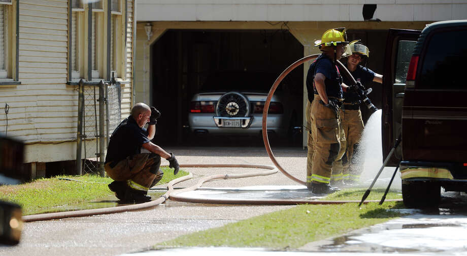 A firefighter crouches behind others as they saturate a vehicle that was the site of a fire on Avenue A on Wednesday morning. First responders must battle the heat of not only a blazing fire but also the triple digit summer temperatures in heavy gear. Beaumont firefighters responded to a fire in the 2300 block of Avenue A on Wednesday morning.  Photo taken Wednesday 8/12/15  Jake Daniels/The Enterprise Photo: Jake Daniels / ©2015 The Beaumont Enterprise/Jake Daniels