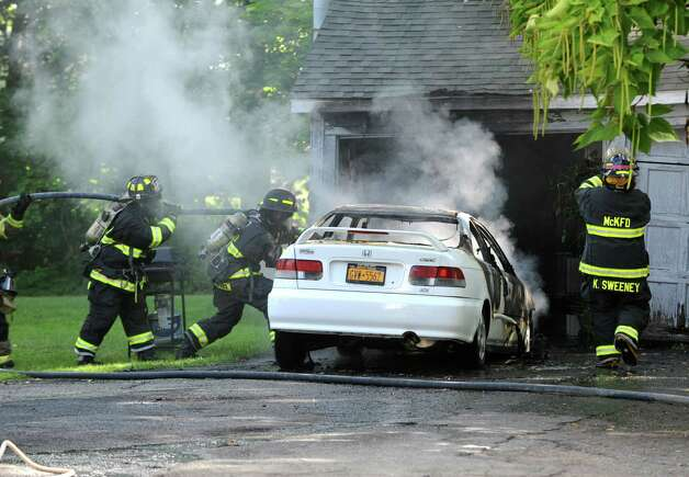 Firefighters work to put out a car fire in the back of a home at 1241 Western Ave. across from Dunkin Donuts on Thursday, Aug. 13, 2015 in McKownville, N.Y.  (Lori Van Buren / Times Union) Photo: Lori Van Buren