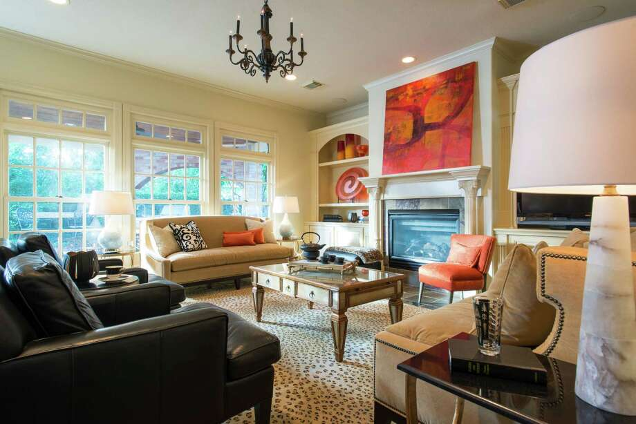 The living room is full of creamy neutrals accented with bright pops of orange, a palette inspired by the Keiko Gonzé¡lez painting above the fireplace. Photo: Michael Hunter