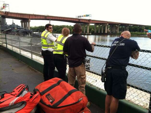 Medical workers wait at the edge of the Hudson River in Albany as officials speak with a man who was sitting on a railing on the Dunn Memorial Bridge over the Hudson River. (Michael P. Farrell / Times Union)