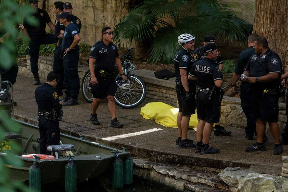 Police stand on the River Walk near the Houston Street bridge in San Antonio, Texas after recovering a drowned body. Photo: Ray Whitehouse, Staff / San Antonio Express-News / 2015 San Antonio Express-News