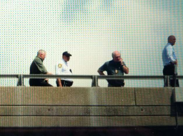 Rescue workers monitor a man sitting on the rail of the Dunn Memorial Bridge between Albany and Rensselaer on Thursday, Aug. 13, 2015. (Michael P. Farrell/Times Union)