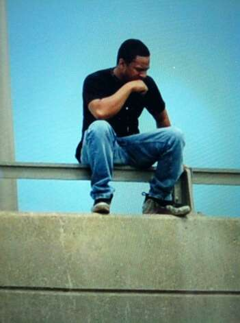 A man sits on the rail of the Dunn Memorial Bridge between Albany and Rensselaer on Thursday, Aug. 13, 2015. Police were trying to convince the man to come down from the railing. (Michael P. Farrell/Times Union)