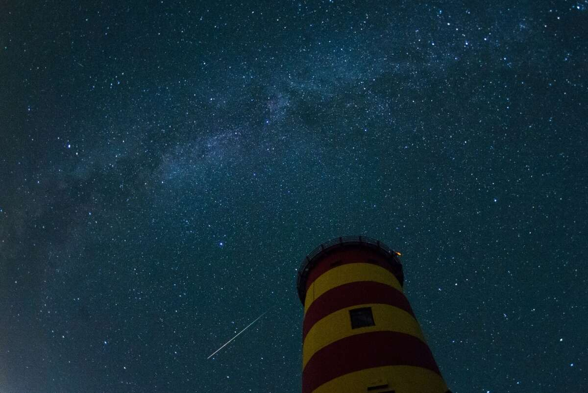 A falling star crosses the night sky behind the lighthouse in Pilsum, northwestern Germany, during the peak in activity of the annual Perseids meteor shower on August 13, 2015. The Perseids meteor shower occurs every year when the Earth passes through the cloud of debris left by Comet Swift-Tuttle. AFP PHOTO / DPA / MATTHIAS BALK +++ GERMANY OUT (Photo credit should read MATTHIAS BALK/AFP/Getty Images)