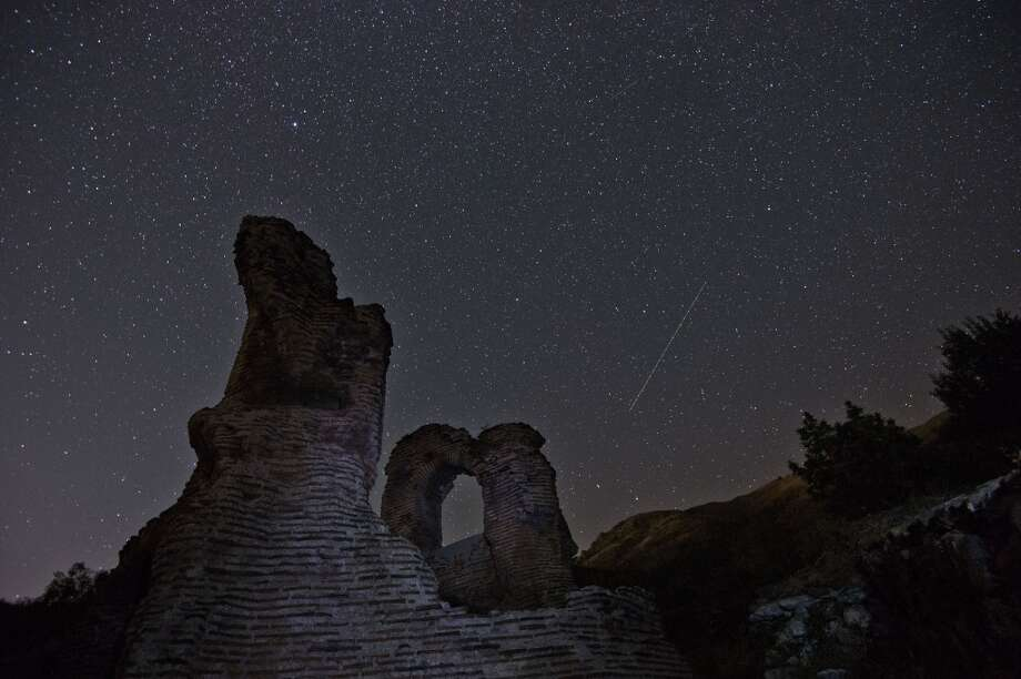 A long exposure image showing a Perseids meteor (R) streaking across the night sky over the remains of St. Ilia Roman early Christian basilica dated back to the 5th6th century AD near the town of Pirdop, early on August 12, 2015. The Perseid meteor shower occurs every year in August when the Earth passes through the debris and dust of the Swift-Tuttle comet. The Perseid meteor shower -- an annual display of natural fireworks -- should be particularly spectacular this year, with extra-dark skies expected to create optimal stargazing conditions, astronomers said on August 7, 2015.   AFP PHOTO / NIKOLAY DOYCHINOV        (Photo credit should read NIKOLAY DOYCHINOV/AFP/Getty Images) Photo: AFP/Getty Images