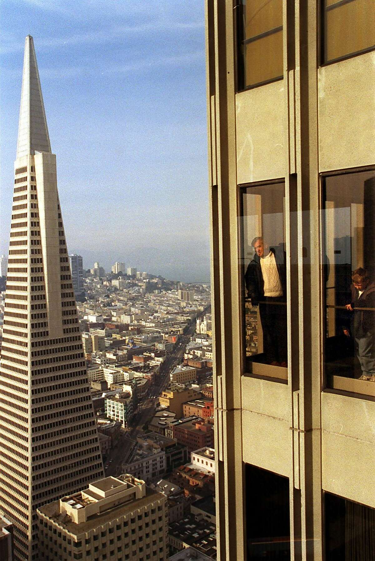 SKYDECK/C/24DEC98/MN/RW Marty Provost and his son James, 10, of San Ramon look out windows of Skydeck with the Transamerica Pyramid in the background at the Embarcadero Center 1 in downtown San Francisco. BY ROBIN WEINER/THE CHRONICLE