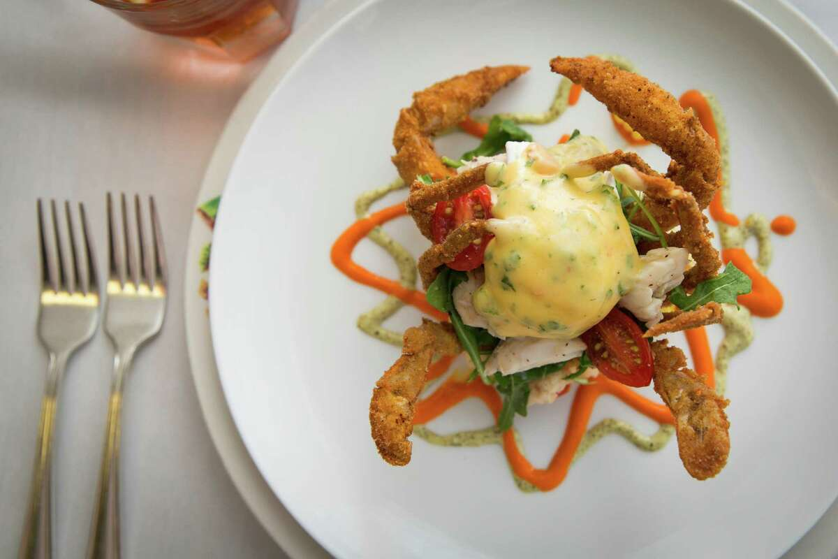 Soft shell crab and eggs,served over grits with greens, tomato, lump crab meat,at Commanders Palace in New Orleans.
