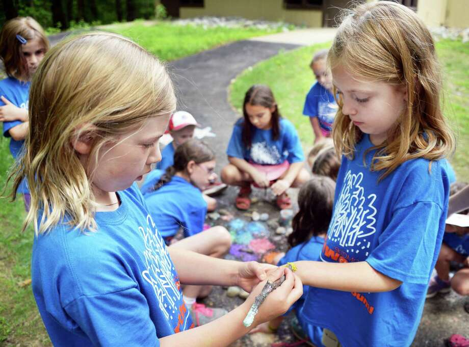 Shannon Cogan, 7, left, paints fellow camper Carina Schneider's hand at Camp Northwoods, a summer day camp held on Skidmore College's Campus Thursday August 13, 2015 in Saratoga Springs, NY.  (John Carl D'Annibale / Times Union) Photo: John Carl D'Annibale / 00032744A