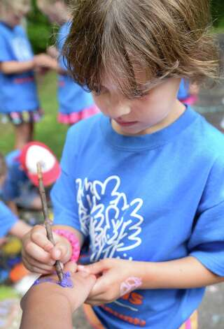Six-year-old Maggie Taylor paints a fellow camper's hand at Camp Northwoods, a summer day camp held on Skidmore College's Campus Thursday August 13, 2015 in Saratoga Springs, NY.  (John Carl D'Annibale / Times Union) Photo: John Carl D'Annibale / 00032744A