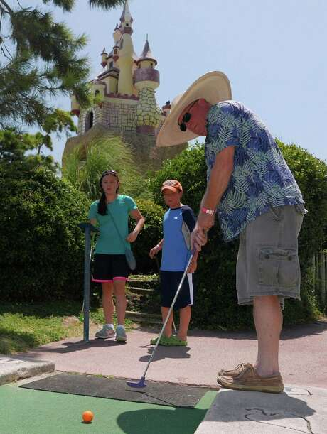 Gilbert Bower putts at Malibu Grand Prix miniature golf in the summer heat on Tuesday, Aug. 11, 2015. Bower is a science teacher in the Medina Independent School District and was enjoying his own last day of summer before reporting to school to teach. His children, Abigail and Gabriel, watch. Photo: Billy Calzada, Staff / San Antonio Express-News / San Antonio Express-News