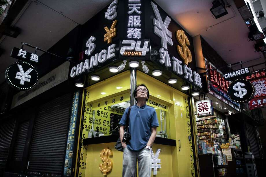 A man stands in front of a foreign currency exchange booth in Hong Kong on Thursday.China cut the reference rate for its currency for the third straight day. Photo: Philippe Lopez /AFP / Getty Images / AFP