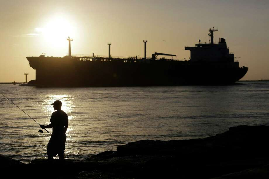 An oil tanker passes a fisherman as it enters a channel near Port Aransas. A line of roughly 40 tankers has formed off the coast of Texas. Photo: Associated Press File Photo / AP