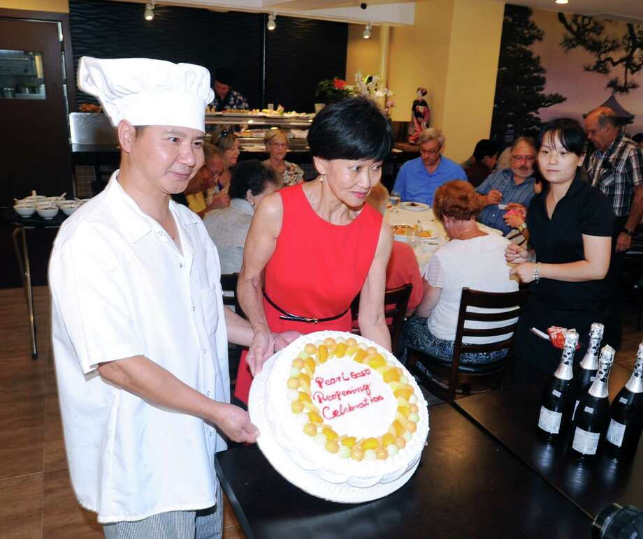 Chef Ye, left, and Ivy Bacher, center, owners of Pearl East, bring out the cake during the grand reopening of the popular Chinese & Japanese restaurant that burned down last year and now is located at 323 Hope Street in Stamford, Conn., Thursday, Aug. 13, 2015. Photo: Bob Luckey Jr. / Hearst Connecticut Media / Greenwich Time