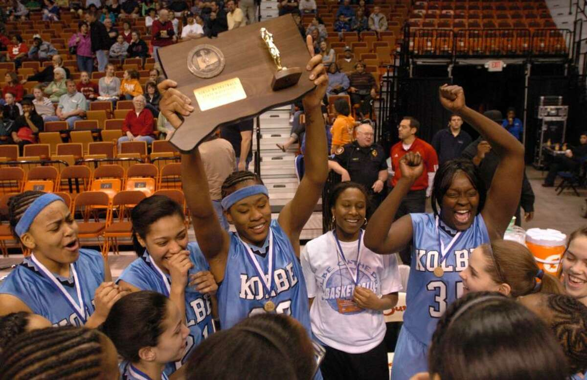 Kolbe's 23, Tiarrah Thompson, center, holds the championship plack after their team won the championship girls basketball game at Mohegan Sun, Friday, March 19, 2010.