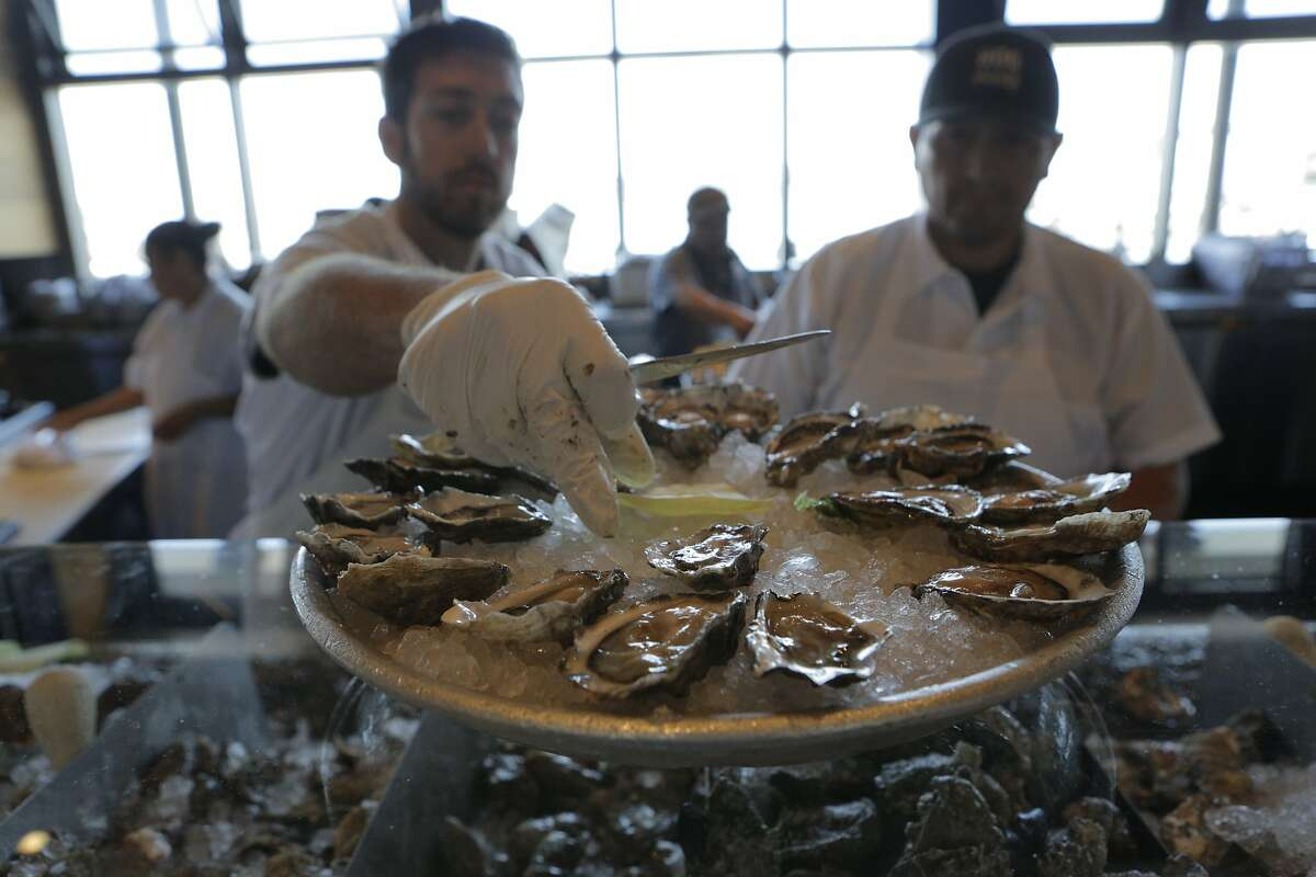 Oyster shuckers Ethan Thompson (left) and Koky Delgado work at Hog Island Oyster Company's restaurant at the Ferry Building Marketplace in San Francisco, Calif., on Thursday, July 16, 2015. Oysters are sent straight from aerated tanks in Marshall to the San Francisco restaurant most days.