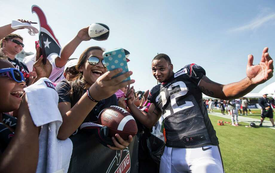 Houston Texans running back Chris Polk (22) poses for a photo for a fan while signing autographs during Texans training camp at the Methodist Training Center Tuesday, Aug. 11, 2015, in Houston. Photo: Brett Coomer /Houston Chronicle / © 2015 Houston Chronicle