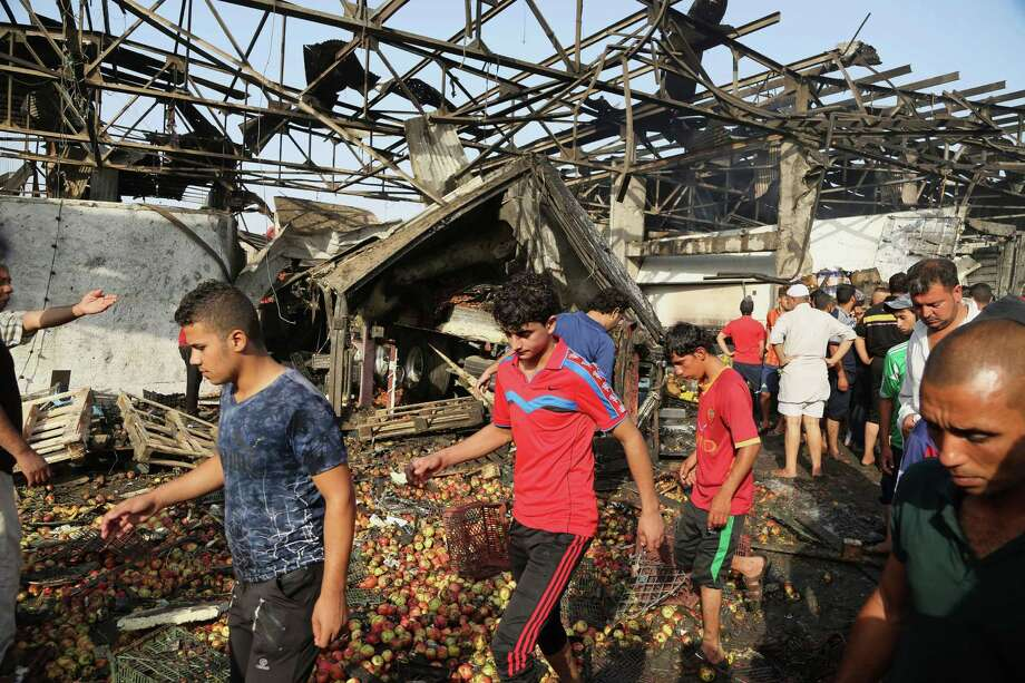 People gather at the scene of a truck bomb attack in Jameela market in the predominantly Shiite neighborhood of Sadr City, Baghdad, Iraq, Thursday, Aug. 13, 2015. The massive truck bomb ripped through the popular Baghdad food market in the Iraqi capital's crowded neighborhood in the early morning hours on Thursday, killing tens of people, police officials said, in one of the deadliest single blasts in the capital in years. (AP Photo/Karim Kadim) ORG XMIT: XKK121 Photo: Karim Kadim / AP