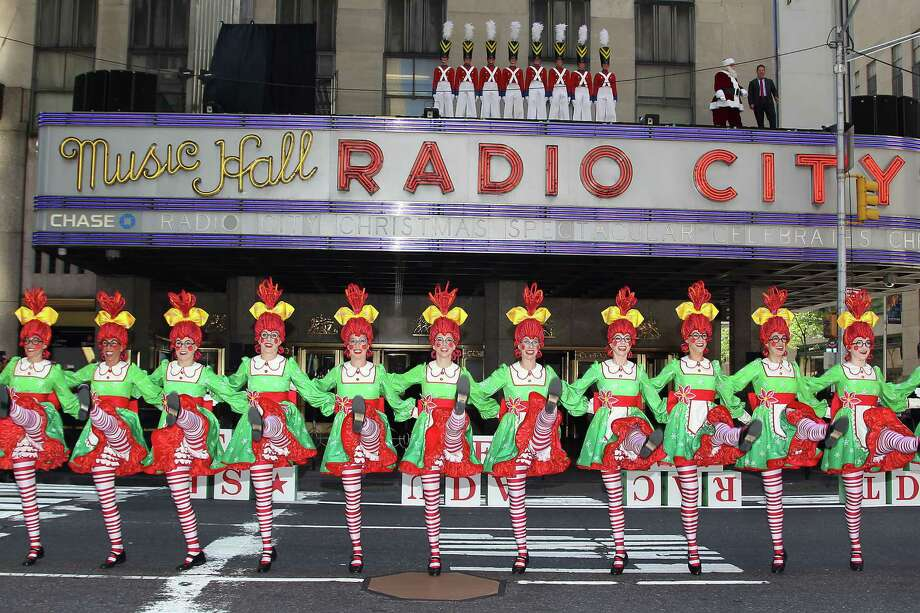 "Father Christmas, along with Rockettes costumed as rag dolls or toy soldiers danced in front of Radio City Music Hall on Thursday, Aug. 13, 2015, performing ""Parade of the Wooden Soldiers"" and the ""Rag Doll"" scene from the ""The Radio City Christmas Spectacular,"" in New York. The brief promotional event happens every year in August, snarling traffic and amusing tourists, to remind patrons that the show will begin Nov. 13 and that tickets are currently on sale. (Kristina Bumphrey/Starpix via AP) ORG XMIT: CAET701 Photo: Kristina Bumphrey / Starpix"
