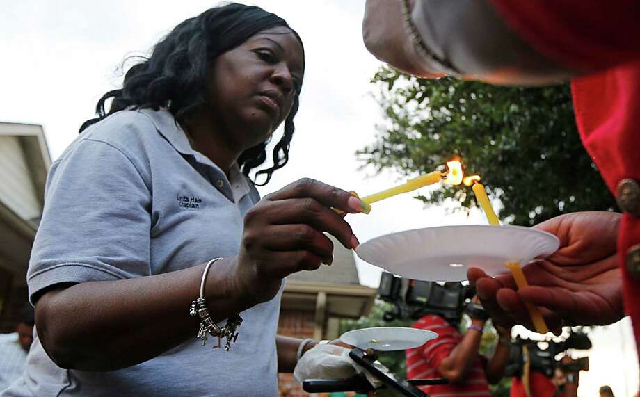 Harris County Sheriff Department Chaplain Lanita Hale left, helps light candles during a prayer vigil at the home of the Jackson family, who were all shot dead over the weekend Thursday, Aug. 13, 2015, in Houston. Photo: James Nielsen, Houston Chronicle / © 2015  Houston Chronicle