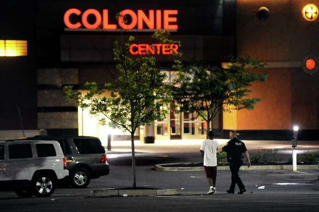 A police officer walks with a witness at the scene of a shooting on Thursday, Aug. 13, 2015, outside Colonie Center in Colonie, N.Y. (Cindy Schultz / Times Union) Photo: Cindy Schultz