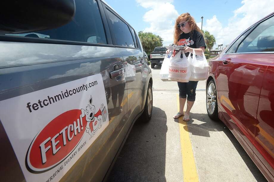 Fetch Delivery's Brandi Miller is loaded with bags while making a lunch delivery for an office in Beaumont Wednesday. After opening in May, the business has quickly grown and is now serving the City of Beaumont in addition to the mid-county region. Photo taken Wednesday, August 5, 2015 Kim Brent/The Enterprise Photo: Kim Brent/The Enterprise