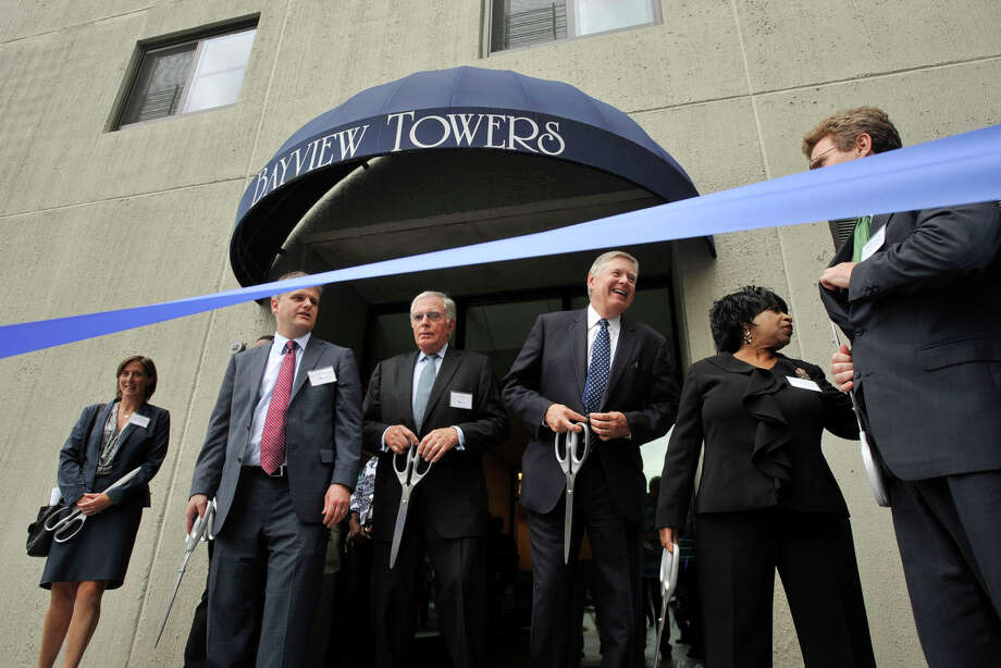 Dara Kovel of the Connecticut Housing Finance Authority, left, commemorates renovations at Bayview Towers in Stamford, Conn., in August 2014 alongside city officials. Photo: Jason Rearick / Jason Rearick / Stamford Advocate