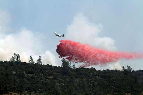 A Department of Forestry and Fire Protection (CAL FIRE) aircraft as it drops fire retardant on August 12, 2015 on a hilltop east of Clearlake, California, during the Jerusalem Fire in Lake County, California.