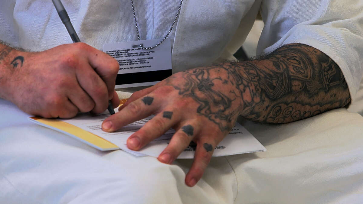 An inmate at Dominguez State Jail completes a questionnaire as part of the