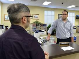 CORRECTS TO SAY THAT THE CLERK'S OFFICE WILL NOT BE ISSUING ANY MARRIAGE LICENSES, REGARDLESS OF WHETHER TO STRAIGHT OR SAME-SEX COUPLES - Rowan County clerk Nathan Davis, right, informs David Moore that the clerk's office will not be issuing any marriage licenses, in defiance of an order from a federal judge in Morehead, Ky., Thursday, Aug. 13, 2015. Rowan County Clerk Kim Davis has already filed a notice of appeal and plans to request a stay on the ruling. (AP Photo/Timothy D. Easley)