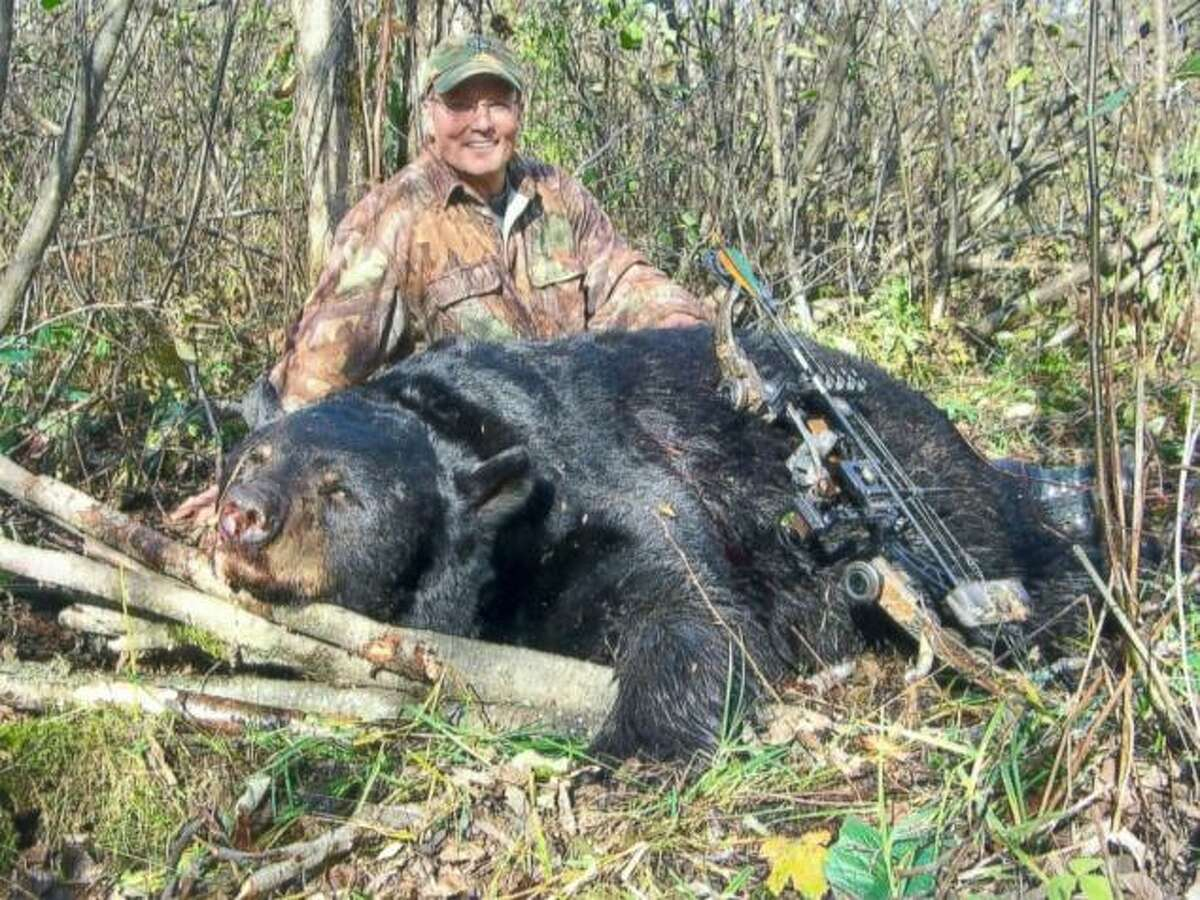 Walter Palmer, the dentist who killed the Zimbabwean lion Cecil, poses with a black bear he shot and killed illegally during a September 2006 hunt in Wisconsin.