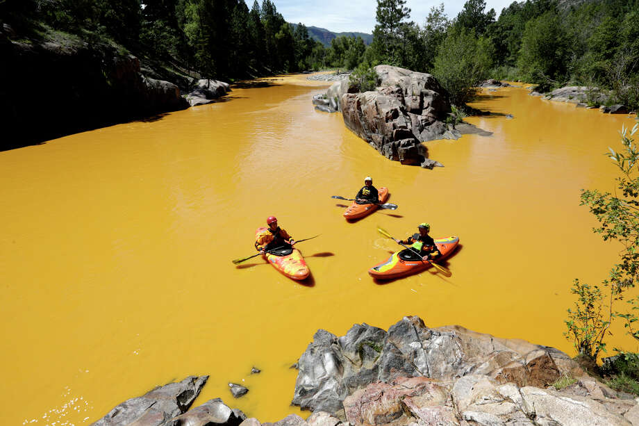 FILE - In this Thursday, Aug. 6, 2015 file photo, people kayak in the Animas River near Durango, Colo., in water colored yellow from a mine waste spill. A crew supervised by the U.S. Environmental Protection Agency has been blamed for causing the spill while attempting to clean up the area near the abandoned Gold King Mine. Tribal officials with the Navajo Nation declared an emergency on Monday, Aug. 10, as the massive plume of contaminated wastewater flowed down the San Juan River toward Lake Powell in Utah, which supplies much of the water to the Southwest. (Jerry McBride/The Durango Herald via AP, FILE) MANDATORY CREDIT ORG XMIT: CODUR201 Photo: Jerry McBride / The Durango Herald