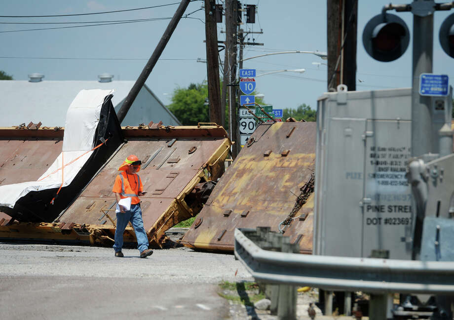 A worker walks along a derailed train on Pine Street on Friday. A train derailed at a crossing on Pine Street near the intersection with Interstate 10 on Friday. The four flatbed cars affected were empty of cargo.  Photo taken Friday 8/14/15  Jake Daniels/The Enterprise Photo: Jake Daniels / ©2015 The Beaumont Enterprise/Jake Daniels