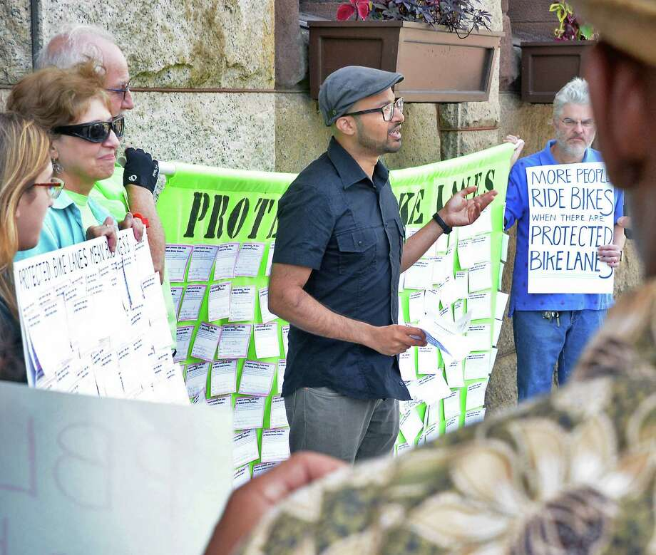Jason D'Cruz, center, of Albany's Protected Bicycle Lane Coalition speaks during a rally calling for a protected bicycle lane for Madison Avenue at City Hall Friday August 14, 2015 in Albany, NY.  (John Carl D'Annibale / Times Union) Photo: John Carl D'Annibale / 00033001A