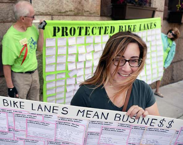 Erin Reale, center, holds a placard during a rally by Albany's Protected Bicycle Lane Coalition calling for a protected bicycle lane for Madison Avenue at City Hall Friday August 14, 2015 in Albany, NY.  (John Carl D'Annibale / Times Union) Photo: John Carl D'Annibale / 00033001A