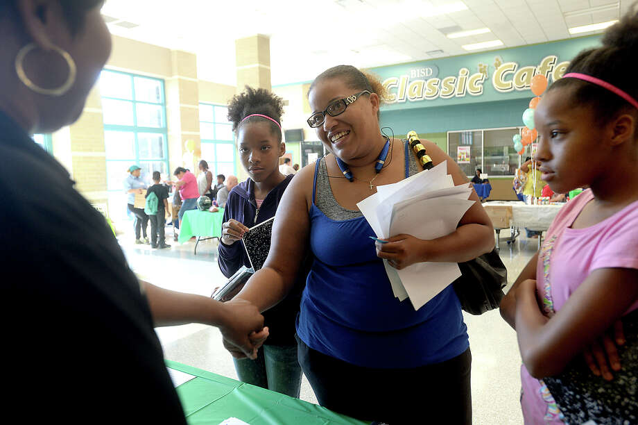 Eighth grade science teacher Robin Ceaser greets Tisha Martin as she stops to pick up supplies for twin daughters Denae Martin (left) and Lenae, 12, during Friday's school orientation and backpack and school supply give-away at South Park Middle School in Beaumont. New and returning students learned their class schedules and had the opportunity to meet staff and sign up for a variety of extracurricular activities, ranging from poetry clubs to sports and student council. A number of community organizations and businesses were also on-hand, offering free give-aways to promote health and wellness. The Food Bank provided boxes of non-perishable items to families, as well. Monday, August 24, is the first day of classes for students in the Beaumont Independent School District. Photo taken Friday, August 14, 2015 Kim Brent/The Enterprise Photo: Kim Brent / Beaumont Enterprise