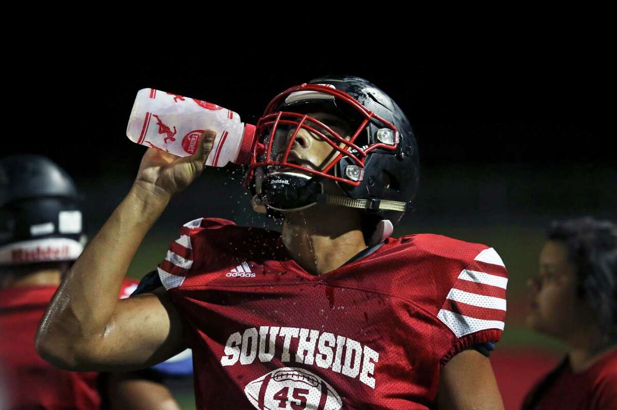 Despite cool temperatures, players sweat in the humid air as the Southside Cardinals hold football practice in their stadium a starting at midnight on Friday, August 14, 2015.