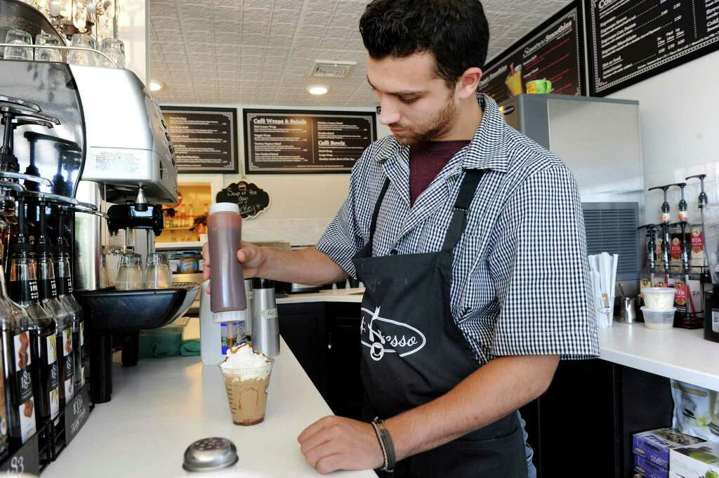 Nico Saraceni, of Bethel, makes a salted caramel mocha latte for a customer at Cafe Xpresso Thursday, August 14, 2015. Cafe Xpresso, is a new business opened in Newtown by Marie and Bob Schlump. Photo: Carol Kaliff / Hearst Connecticut Media / The News-Times