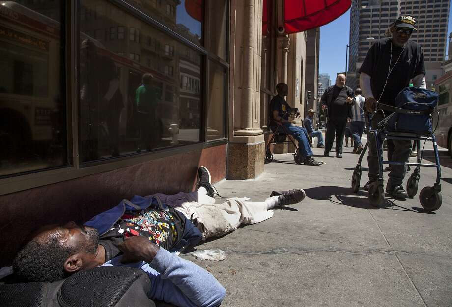 Andre Pierre Thurston sleeps outside Glide Memorial Church in the Tenderloin neighborhood in San Francisco, which bars sitting or lying on sidewalks between 7 a.m. and 11 p.m. Photo: Santiago Mejia, Special To The Chronicle