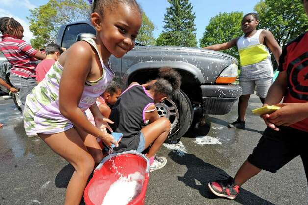 Seven-year-old Niasia Howard joins other children from a Boys and Girls Club summer program washed cars and sold lemonade to raise money to fix up Steinmetz Park in Schenectady's Goose Hill neighborhood on Friday Aug. 14, 2015 in Schenectady, N.Y.  (Michael P. Farrell/Times Union) Photo: Michael P. Farrell / 00033007A