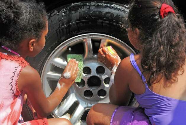 Alexia Bynoe, 7, left, and Neveah Ayala, 9, join other children from a Boys and Girls Club summer program washed cars and sold lemonade to raise money to fix up Steinmetz Park in Schenectady's Goose Hill neighborhood on Friday Aug. 14, 2015 in Schenectady, N.Y.  (Michael P. Farrell/Times Union) Photo: Michael P. Farrell / 00033007A
