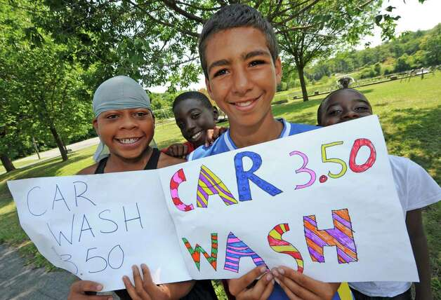 Left to right, Jonte Darkins, Justin Ghee, Eric Washington and Tarell Dupree and other children from a Boys and Girls Club summer program washed cars and sold lemonade to raise money to fix up Steinmetz Park in Schenectady's Goose Hill neighborhood on Friday Aug. 14, 2015 in Schenectady, N.Y.  (Michael P. Farrell/Times Union) Photo: Michael P. Farrell / 00033007A