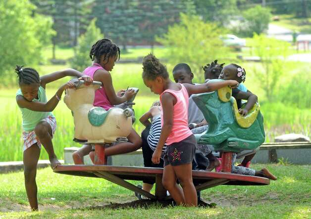 Children from a Boys and Girls Club summer program take a break in the park between washing cars and selling lemonade to raise money to fix up Steinmetz Park in Schenectady's Goose Hill neighborhood on Friday Aug. 14, 2015 in Schenectady, N.Y.  (Michael P. Farrell/Times Union) Photo: Michael P. Farrell / 00033007A